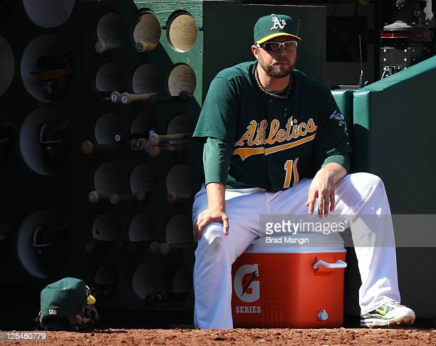 Landon Powell of the Oakland Athletics sits in the dugout against the Detroit Tigers during the game at Oco Coliseum on September 17 2011 in Oakland...