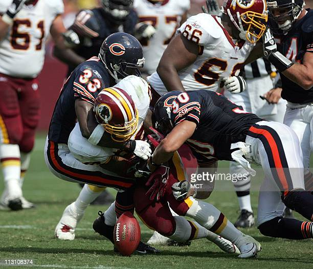 Landover MD Washington Redskins running back Clinton Portis fumbles the ball as he is tackled by Chicago Bears Charles Tillman left and Mike Brown...