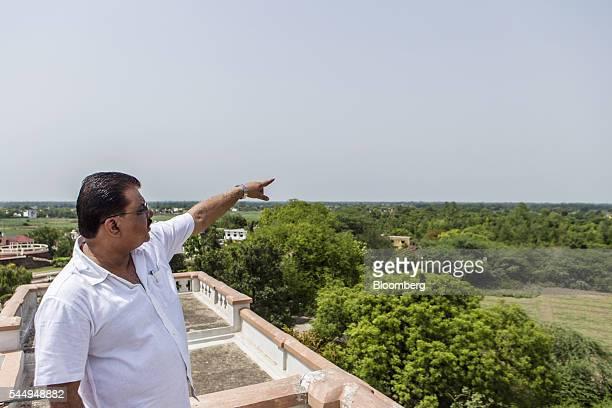 Landowner Kunwar Vikram Jeet Singh gestures towards his farmland from the roof of his mansion in Kuchesar Uttar Pradesh India on Tuesday May 24 2016...