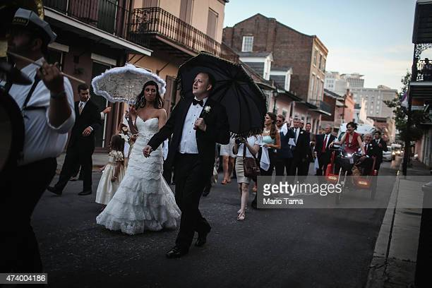 Landrum Hughes and Julie Hughes celebrate their wedding with a 'second line' parade through the French Quarter on May 9 2015 in New Orleans Louisiana...