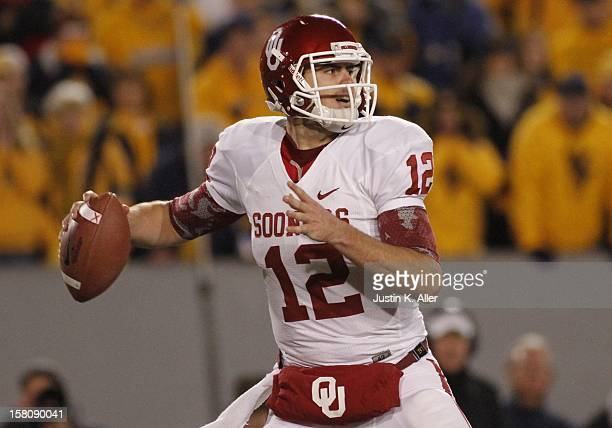 Landry Jones of the Oklahoma Sooners drops back to pass against the West Virginia Mountaineers during the game on November 17 2012 at Mountaineer...