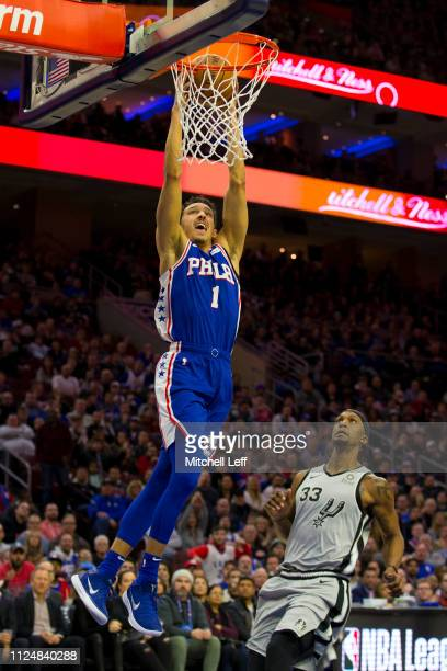 Landry Shamet of the Philadelphia 76ers dunks the ball past Dante Cunningham of the San Antonio Spurs at the Wells Fargo Center on January 23 2019 in...
