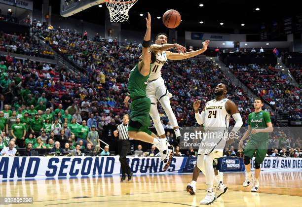 Landry Shamet of the Wichita State Shockers blocks a shot by Jarrod West of the Marshall Thundering Herd in the second half during the first round of...