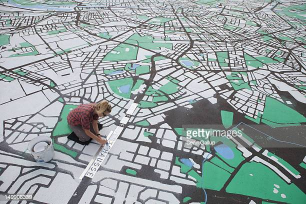 Landscape architect Lisa Hankow paints a giant map of Berlin in the city center on August 6 2012 in Berlin Germany The map which will measure 50...