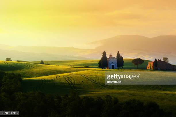 landscape at sunrise in tuscany (with the famous cappella di vitaleta) - capella di vitaleta stock pictures, royalty-free photos & images