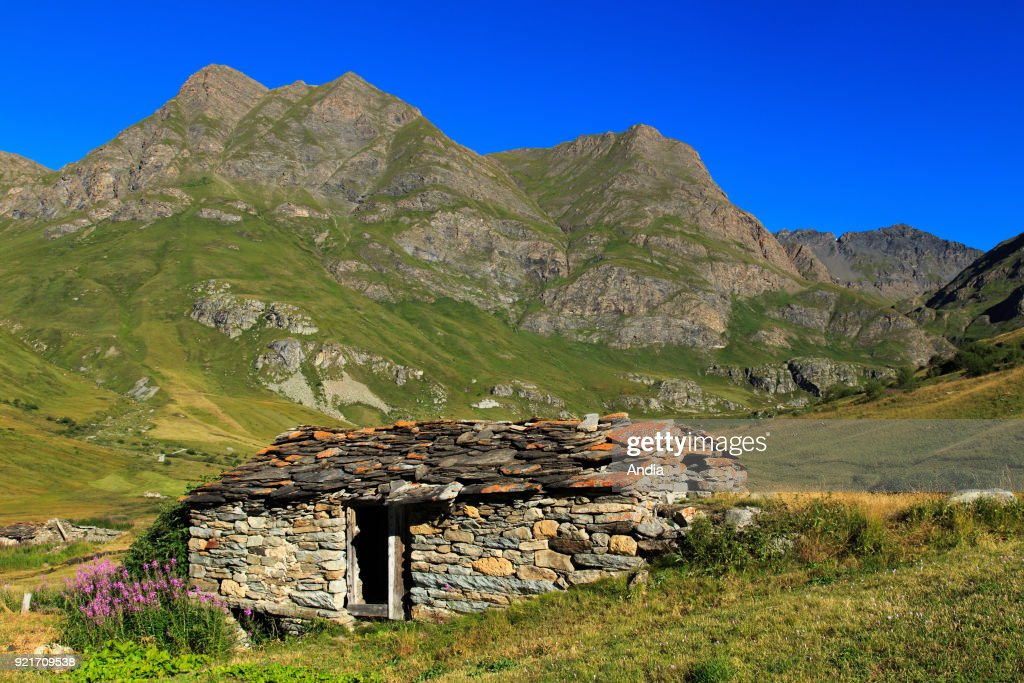 Landscape between the Col de l'Iseran mountain pass and Bonneval-sur-Arc (Savoy, French Alps): stone chalet with flagstone on the roof.