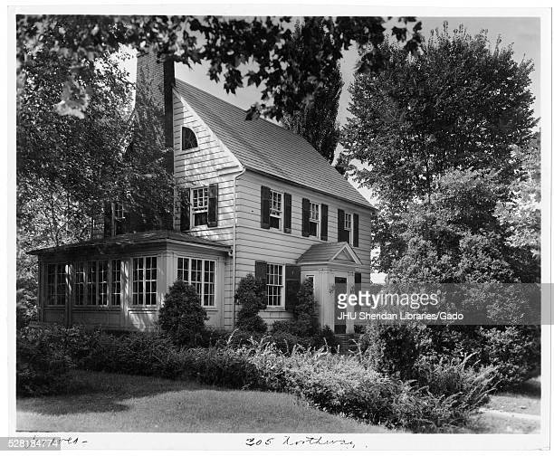 Landscape diagonal shot of a white house with an annexed sun room, surrounded by many trees and shrubs with leaves, Roland Park/Guilford, Baltimore,...