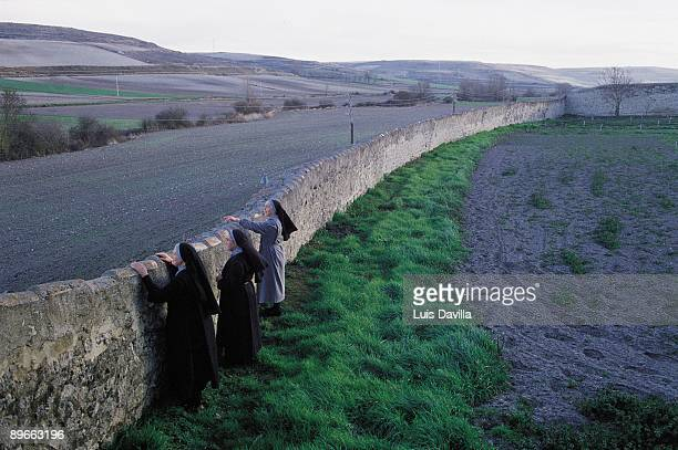 Landscape from a Benedictine convent Three nuns look at the landscape above a wall of the Benedictine convent Palacios Benaver County of Burgos