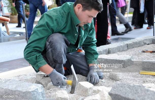 Landscape gardener Andreas Kormpos works at a booth at the Internationale Handwerksmesse in Munich Germany 26 February 2016 More than 1000 exhibitors...