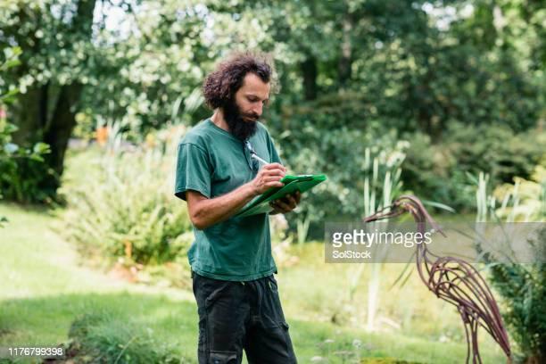 庭のクリップボードにメモを作るランドスケープガーデナー - 造園師 ストックフォトと画像