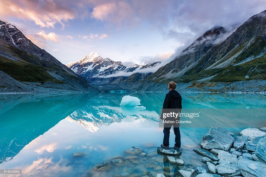 Landscape: hiker looking at Mt Cook from lake with iceberg, New Zealand : Stock Photo
