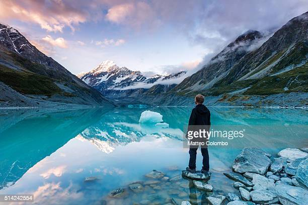 landscape: hiker looking at mt cook from lake with iceberg, new zealand - new zealand stock pictures, royalty-free photos & images