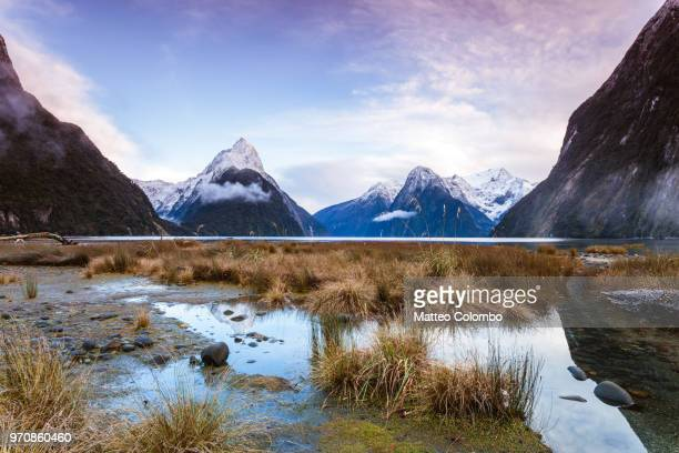 landscape: iconic view of milford sound at sunrise, new zealand - international landmark stock pictures, royalty-free photos & images
