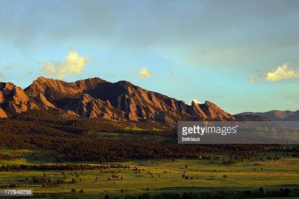 Landscape image of boulder flatirons and a lush field