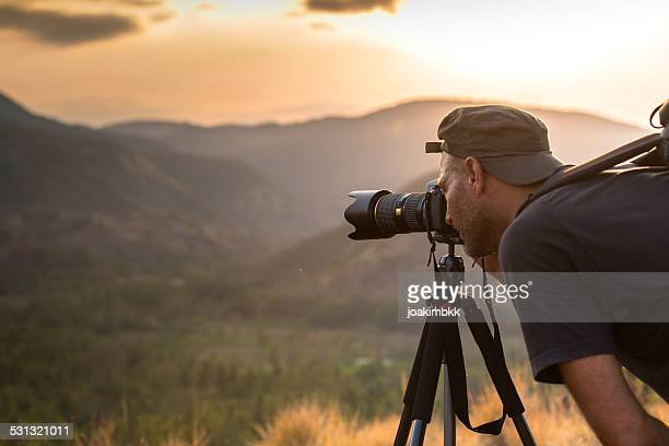 landscape male photographer in action taking picture - photographer stock photos and pictures