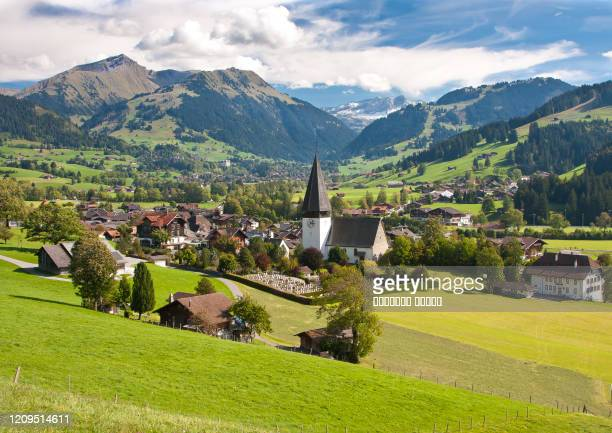 landscape near gstaad, summer view to saanen church and village - グスタード ストックフォトと画像