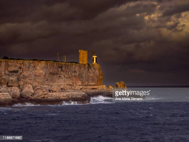 landscape of cala figuera lighthouse with dramatic sky with storm clouds and big waves in the sea - bucht stock-fotos und bilder