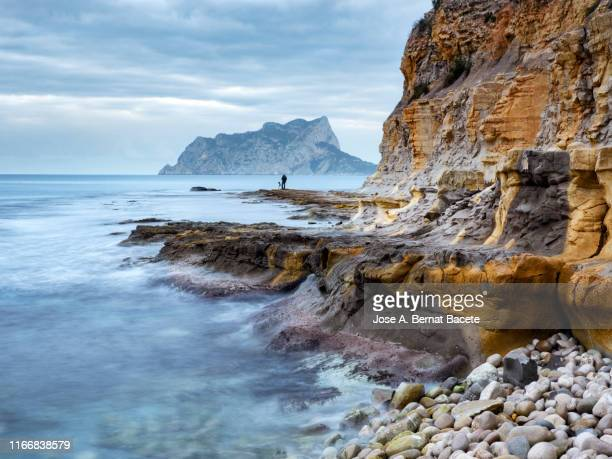 landscape of coast with rocks and the sea in movement. peñon de ifach, alicante, valencian community, spain. - alicante stock pictures, royalty-free photos & images