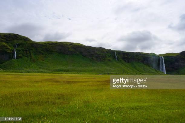 landscape of grasslands and waterfalls under overcast sky - 平地 ストックフォトと画像