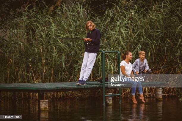 landscape of happy family waiting to fish by the river - riverbank stock pictures, royalty-free photos & images