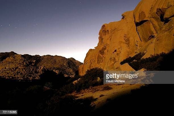 A landscape of huge rock formations comprising the remote desert mountains bisected by the USMexico border is illuminated by the full Harvest Moon...
