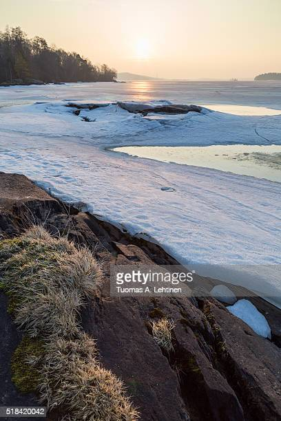 Landscape of rock, frozen lake and cracked ice in Finland in the spring at dawn.
