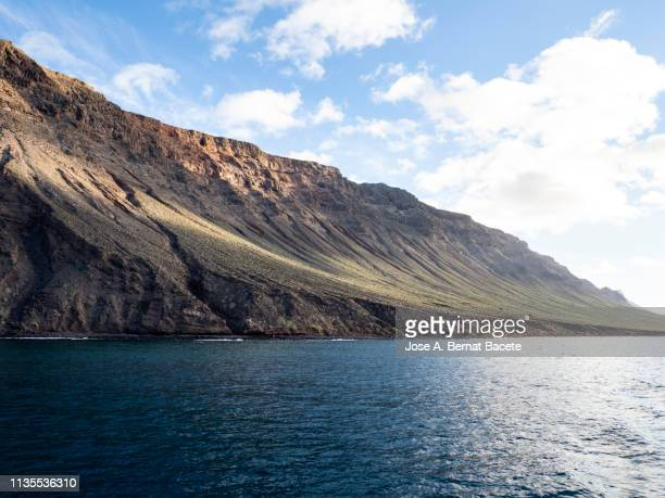 landscape of rocky volcanic coast in the island of lanzarote, canary islands, spain. - arrecife stock photos and pictures