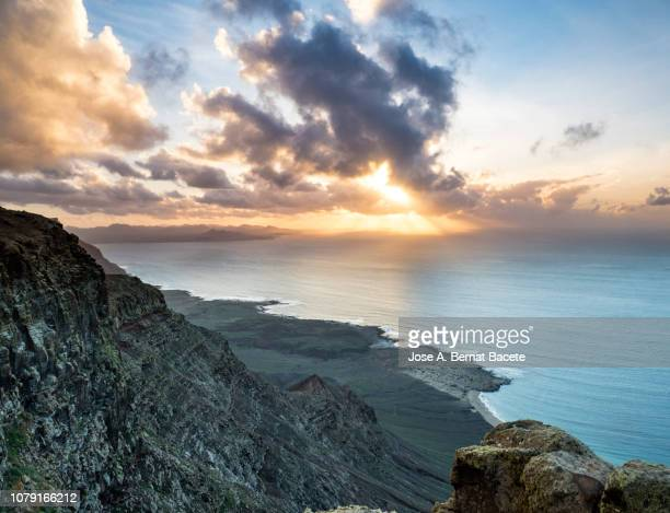 landscape of rocky volcanic coast in the island of lanzarote in the sunset, canary islands, spain. - volcanic rock stock pictures, royalty-free photos & images