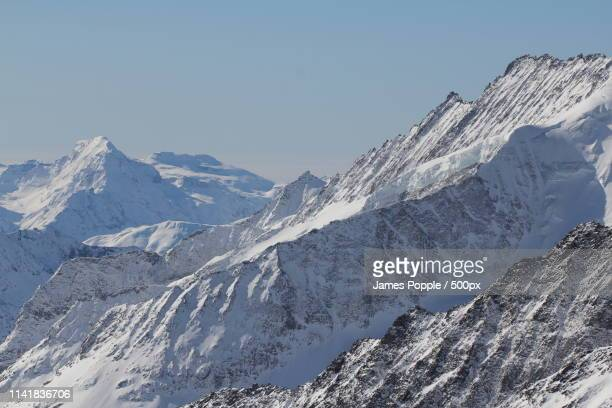 landscape of snowcapped mountains - james popple stock photos and pictures