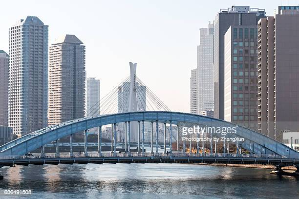 landscape of tokyo chuo ward with eitai bridge and skyscrapes over sumida river at daytime. - 永代橋 ストックフォトと画像