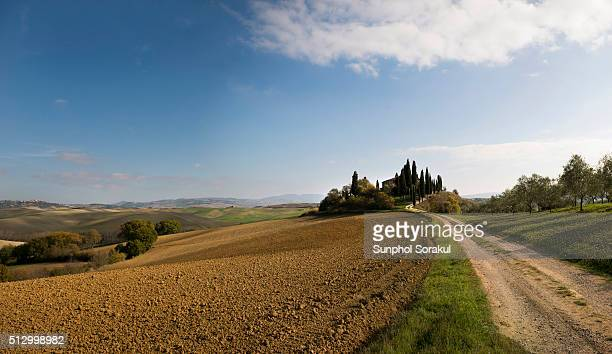 landscape of val d'orcia with dirt road, rolling hills and a house with cypress trees - san quirico d'orcia stock pictures, royalty-free photos & images