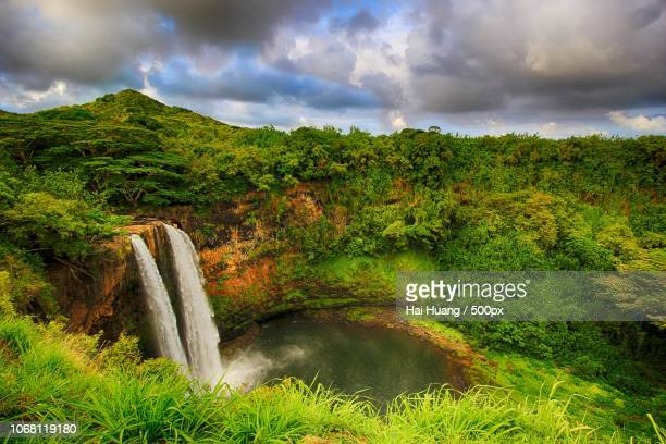 landscape of waterfall flowing in forest under dramatic sky - ghana stock pictures, royalty-free photos & images