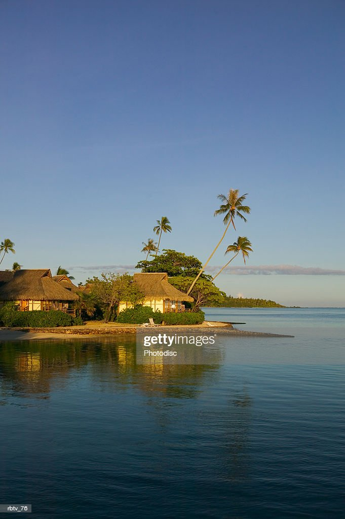 landscape photograph of a beautiful beach and grass huts of a tropical resort : Foto de stock