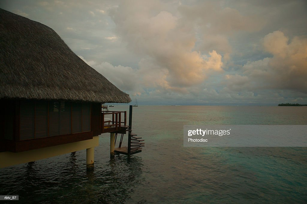 landscape photograph of a grass hut over the water as a tropical storm gathers in the background : Foto de stock