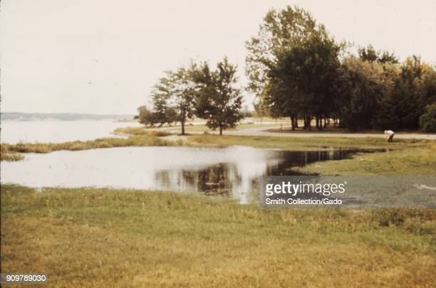 Landscape photograph of a lake reservoir including an area of seepage in a flat grassy area with trees one person pedestrian path and distant hills...