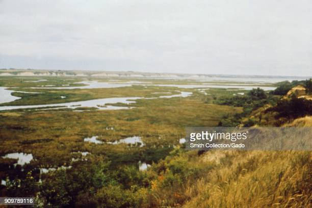 Landscape photograph of a marshy lake reservoir with bluffs visible in the foreground and background taken as part of an investigation into...