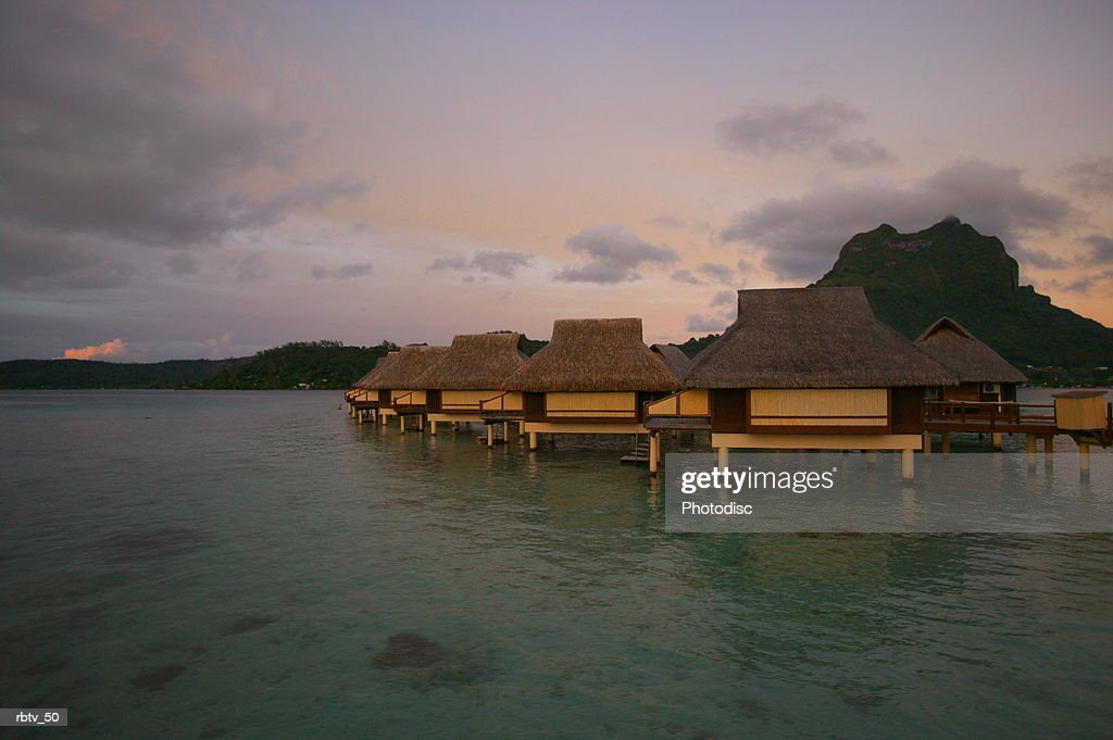 landscape photograph of a tropical resort with grass huts over the water at dusk : Foto de stock