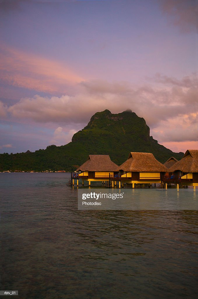 landscape photograph of a tropical resort with huts over the water at sunset : Foto de stock