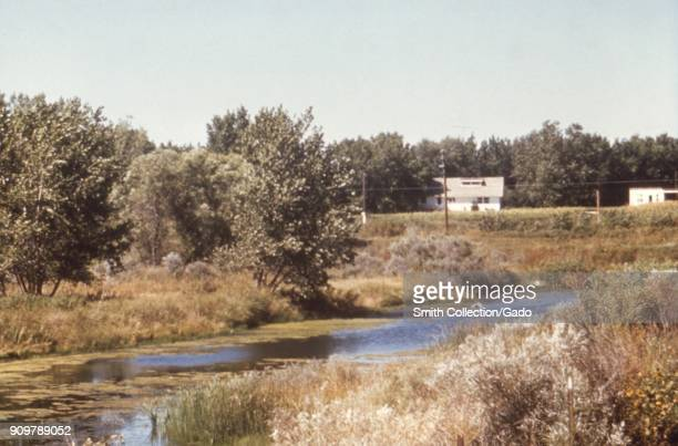 Landscape photograph of a Ushaped oxbow bend in a river with trees two white buildings and overhead power lines visible in the background taken as...