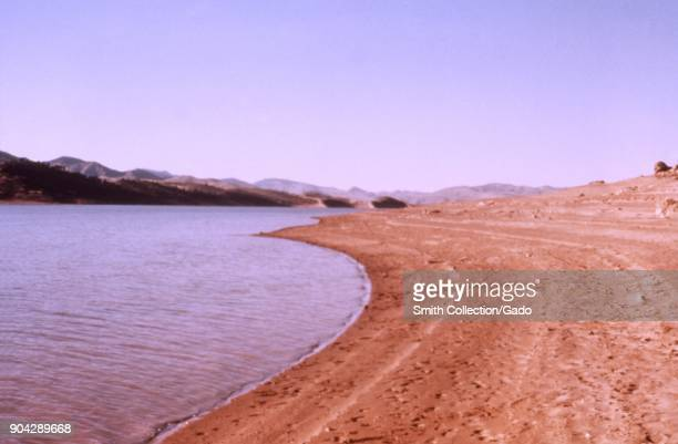 Landscape photograph of an arid red sandstone shoreline at a lake reservoir with distant mountains visible in the background taken as part of an...