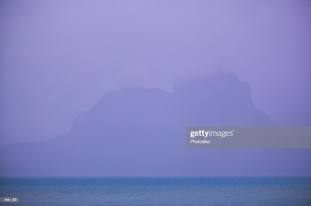 landscape photograph of an island mountain seen through the ocean mist : Foto de stock