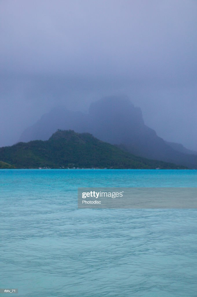 landscape photograph of crystal clear water and tropical mountains through the mist : Foto de stock