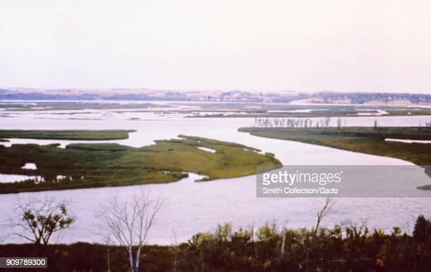 Landscape photograph of grassy islands formed within a lake reservoir set in flat grassy lands with bluffs visible in the background taken as part of...