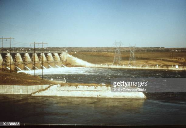 Landscape photograph of spillways at a hydroelectric dam with overhead power lines and pylons also visible taken as part of an investigation into...