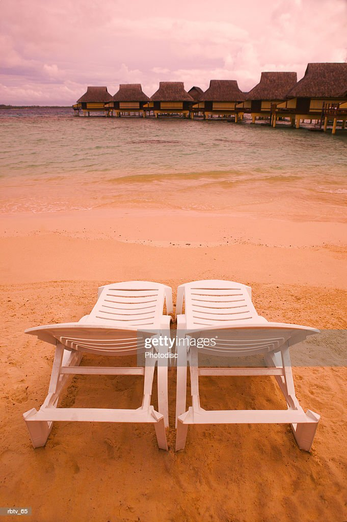 landscape photograph of two empty beach chairs overlooking a beautiful beach and resort : Stock Photo