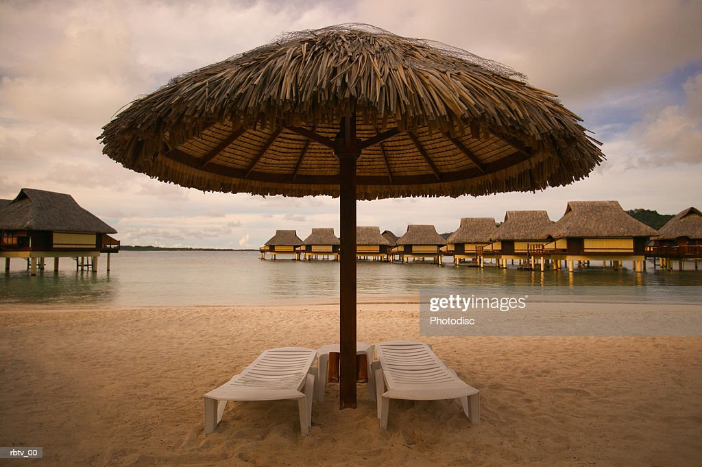 landscape photograph of two empty beach chairs under an umbrella at a tropical resort : Foto de stock