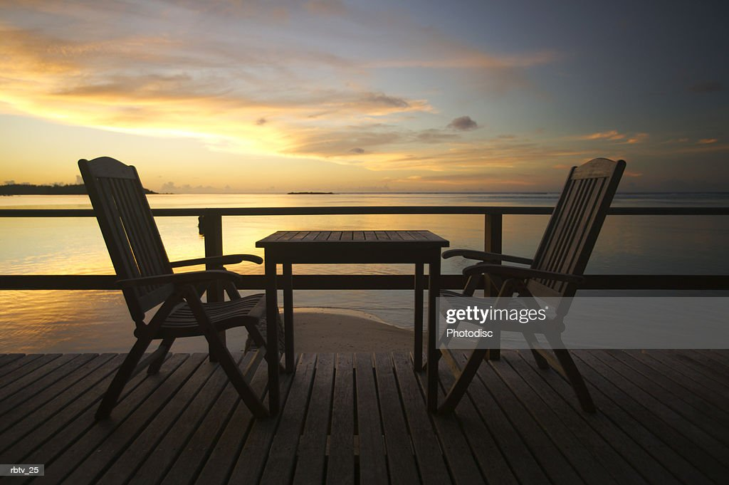 landscape photograph of two empty chairs out on a deck overlooking a beach at sunset : Foto de stock
