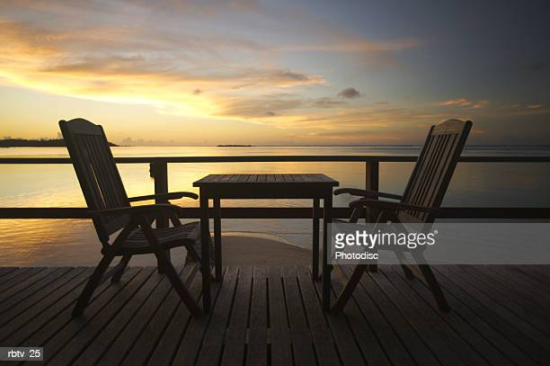 landscape photograph of two empty chairs out on a deck overlooking a beach at sunset
