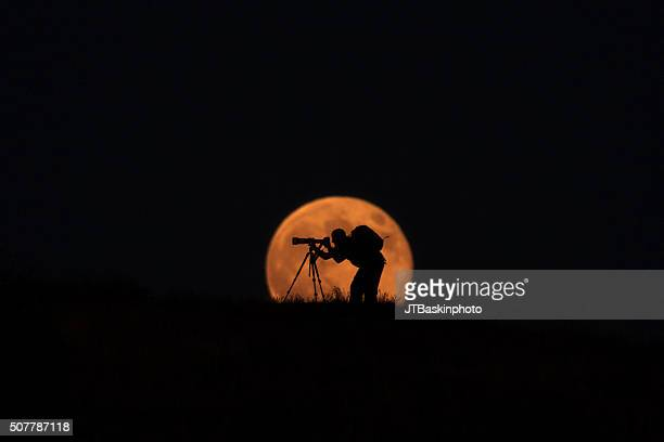 Landscape Photographer Silhouetted Against the Rising Moon