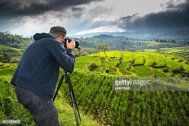 Landscape photographer taking photos of ricefield